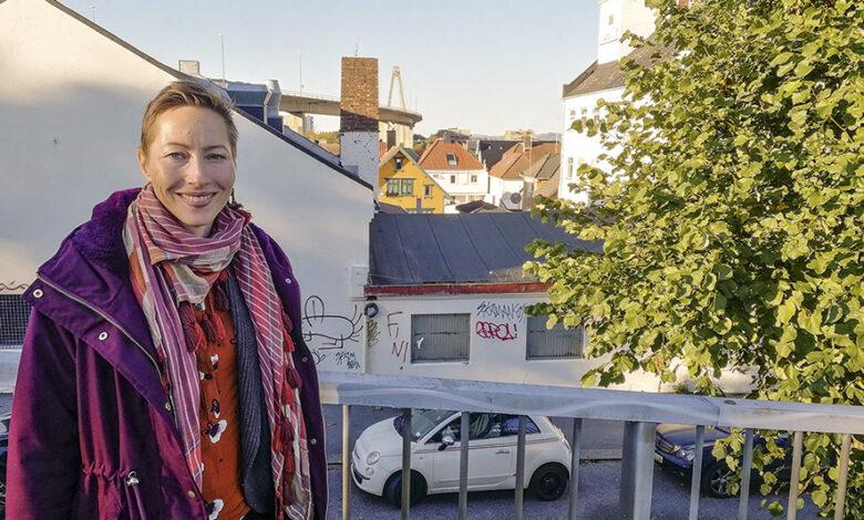 Sara Nustad Mauland på gangbrua ved Kjelvene. I bakgrunnen ses deler av bygninger og fabrikkpipe som foreslås revet. Til høyre bak treet ses litt av «tårnhuset» som skal bevares. Og midt i bildet ses et av bolighusene (gult) i Spilderhauggata som vil få mer skygge og mindre sol.